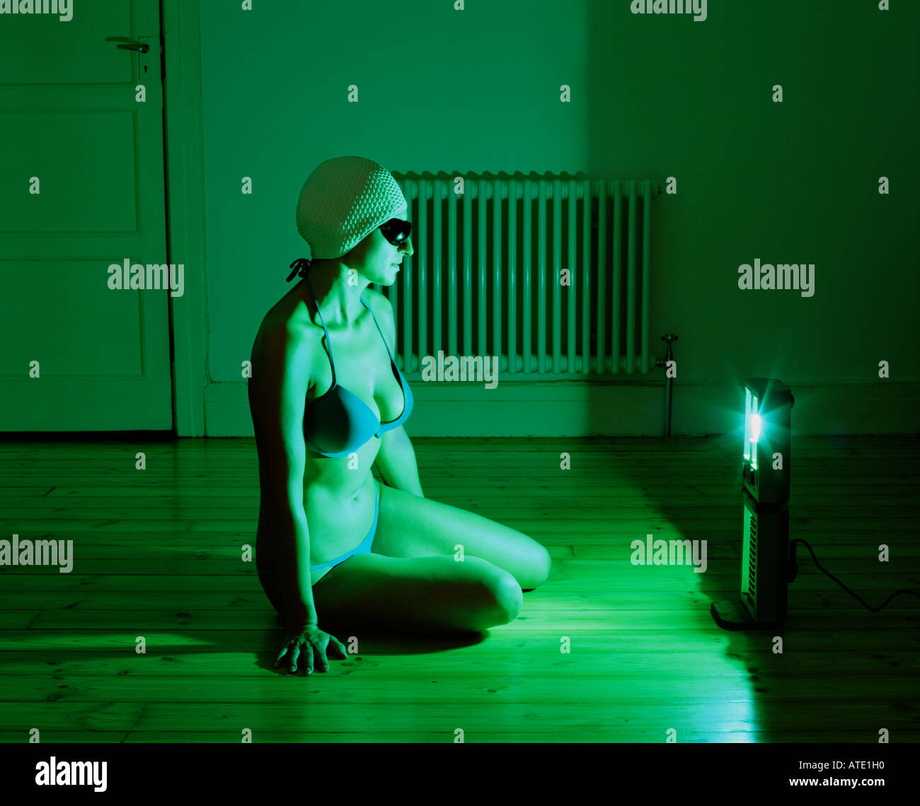 Swimmer sitting in front of tanning lamp - Stock Image