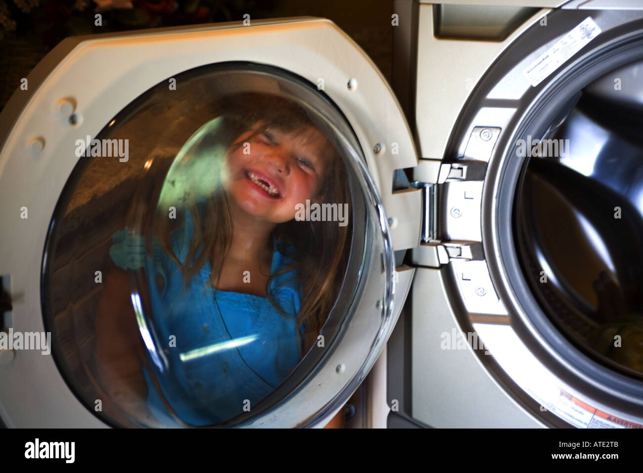 Little girl seen through open door of washing machine - Stock Image