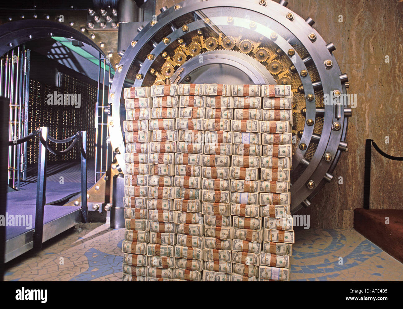 money stacked in front of a bank vault - Stock Image