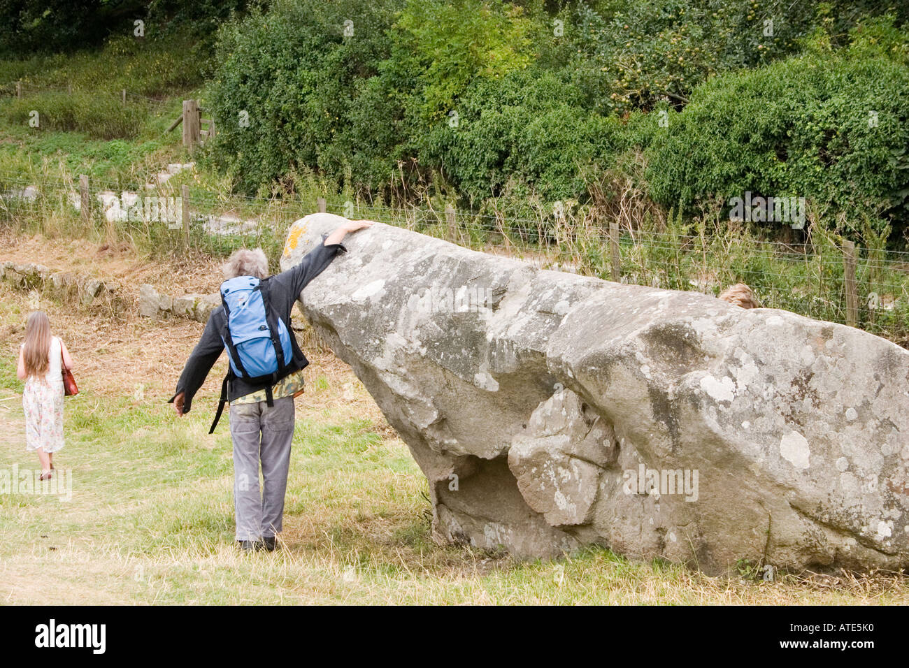 Visitors communing with a huge fallen stone Avebury circle Wiltshire UK - Stock Image