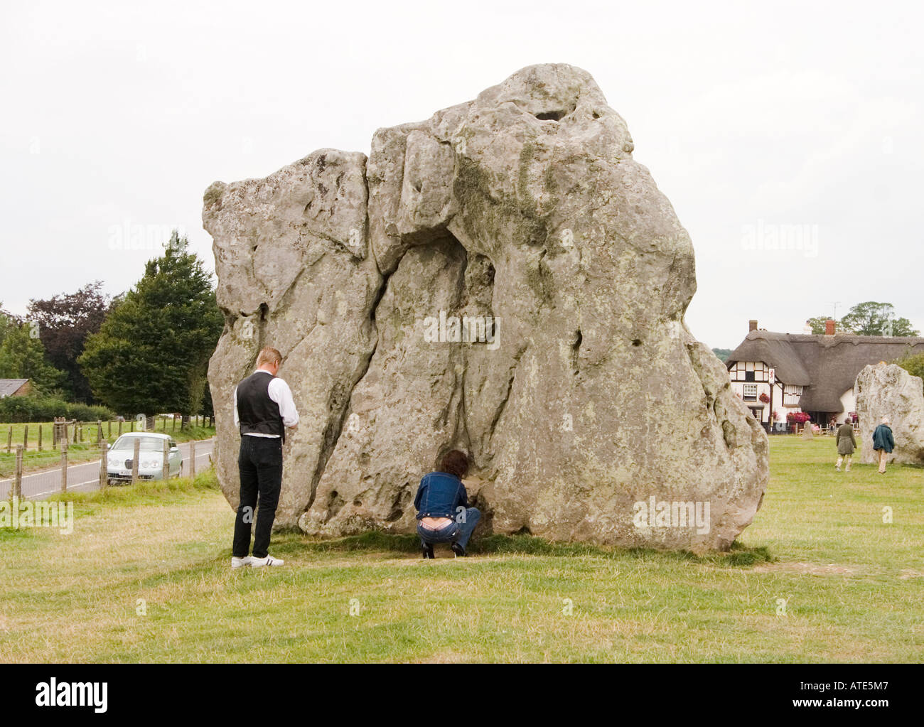 Visitors making an offering in the Avebury stone circle - Stock Image