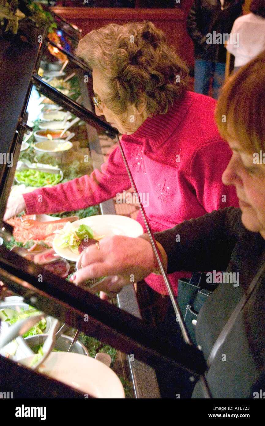 Women age 90 and 62 serving themselves at the Ruby Tuesday restaurant salad bar. Plymouth Minnesota MN USA - Stock Image