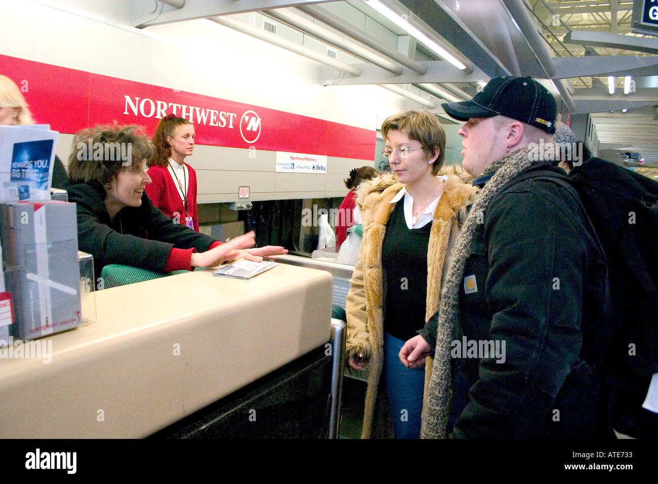 Good natured airline ticket agent trying to explain travel contingencies to weary couple age 28. Minneapolis Minnesota MN USA - Stock Image