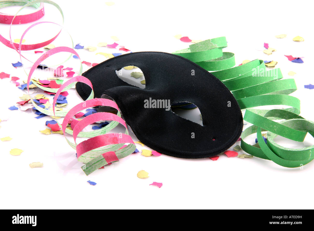 carnival concepts paper confetti streamers and black mask isolated on white background - Stock Image