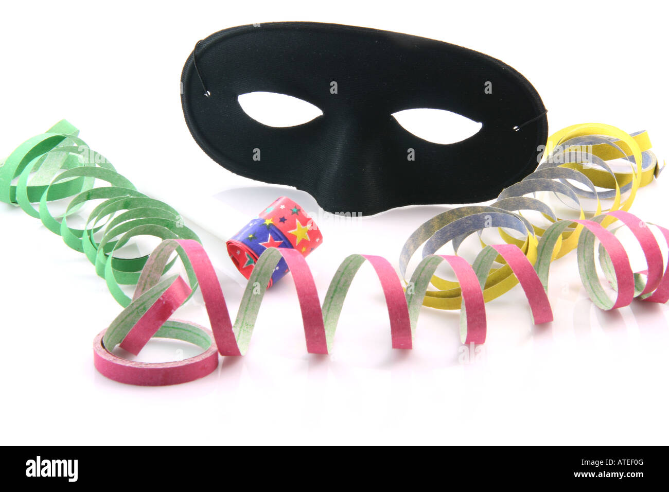 holidays and party time paper streamers party blower and black mask isolated on white background - Stock Image