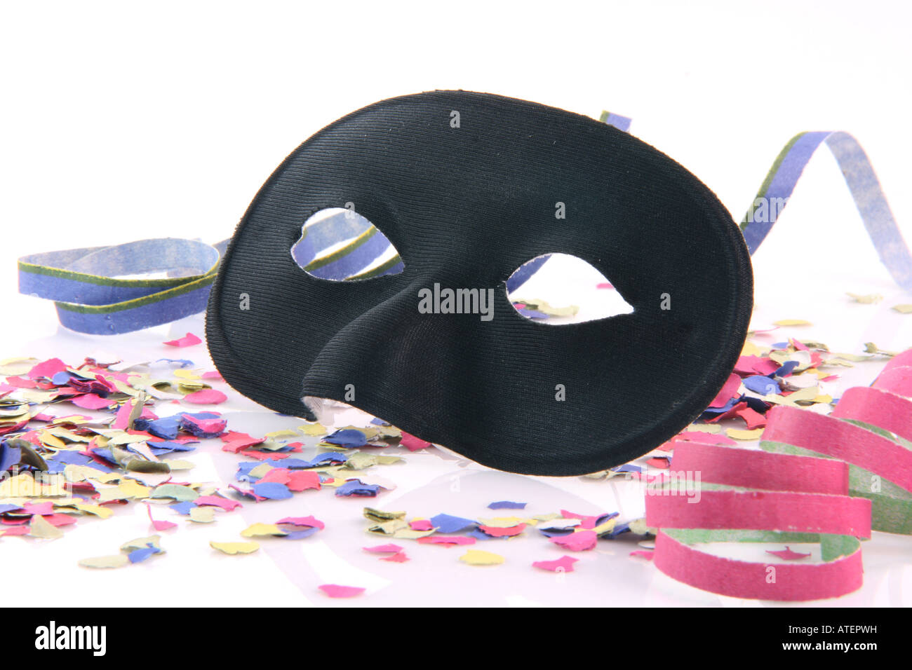 carnival concepts paper closeup black mask with confetti and streamers isolated on white background - Stock Image