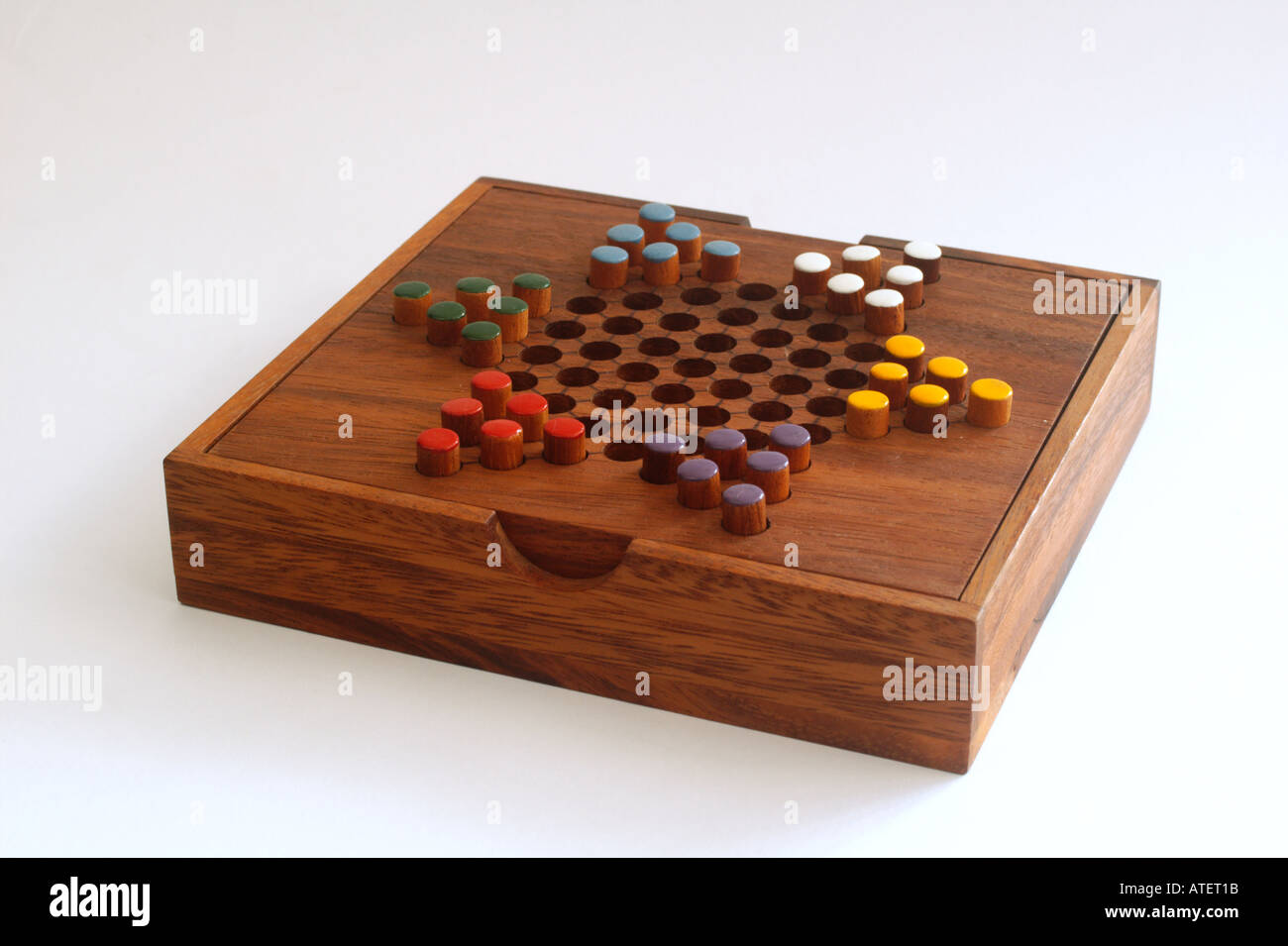 Chinese checkers colour pegs on a wooden board A game of strategy and planning Stock Photo