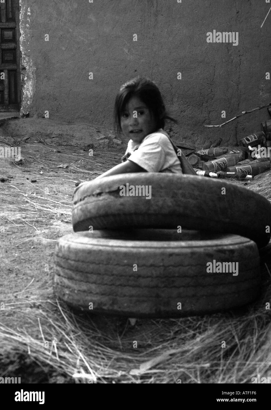 Indigenous child girl smile play outdoor ground rubber tyre dirt junk bottle Sacred Valley Cuzco Peru South Latin America - Stock Image