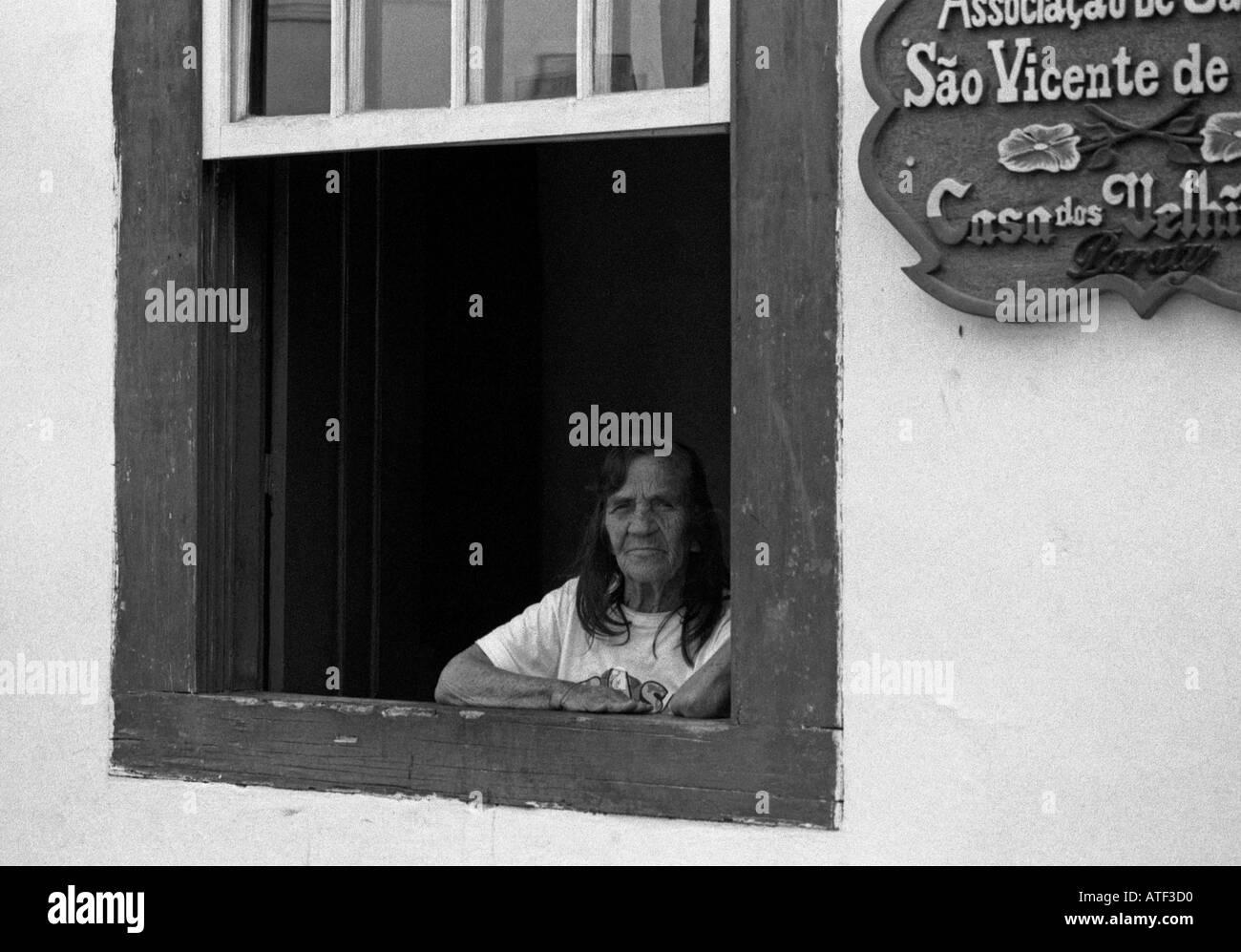 'The Unbearable Lightness of Being' Woman at window of nursing home Paraty Rio de Janeiro Brazil Brasil South Latin America - Stock Image