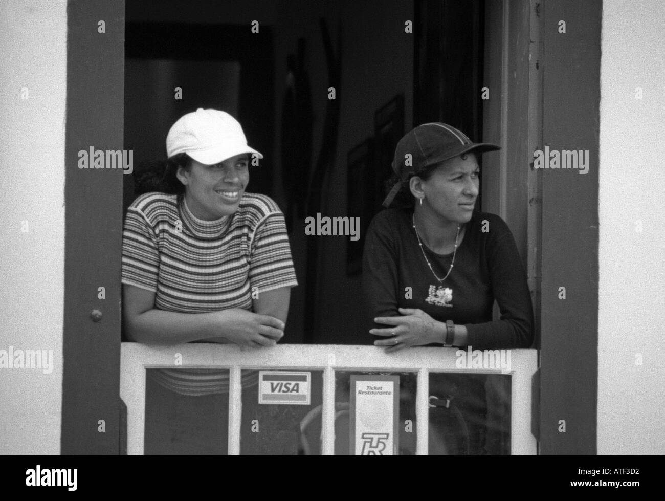 Smiling young women at the window of a souvenir shop Paraty Rio de Janeiro Brazil Brasil South Latin America Stock Photo
