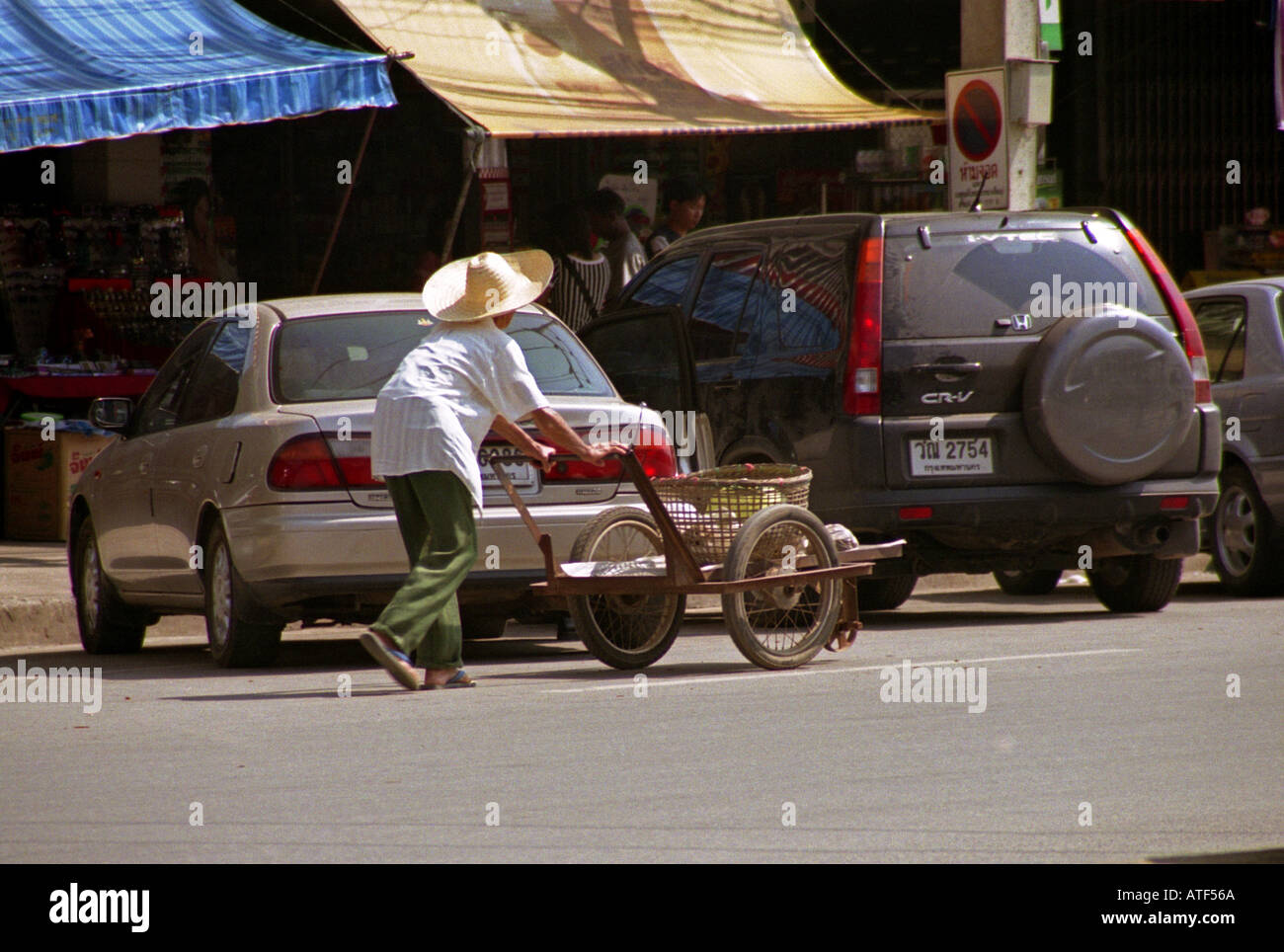 Man with sombrero like hat walk push two wheel cart carry
