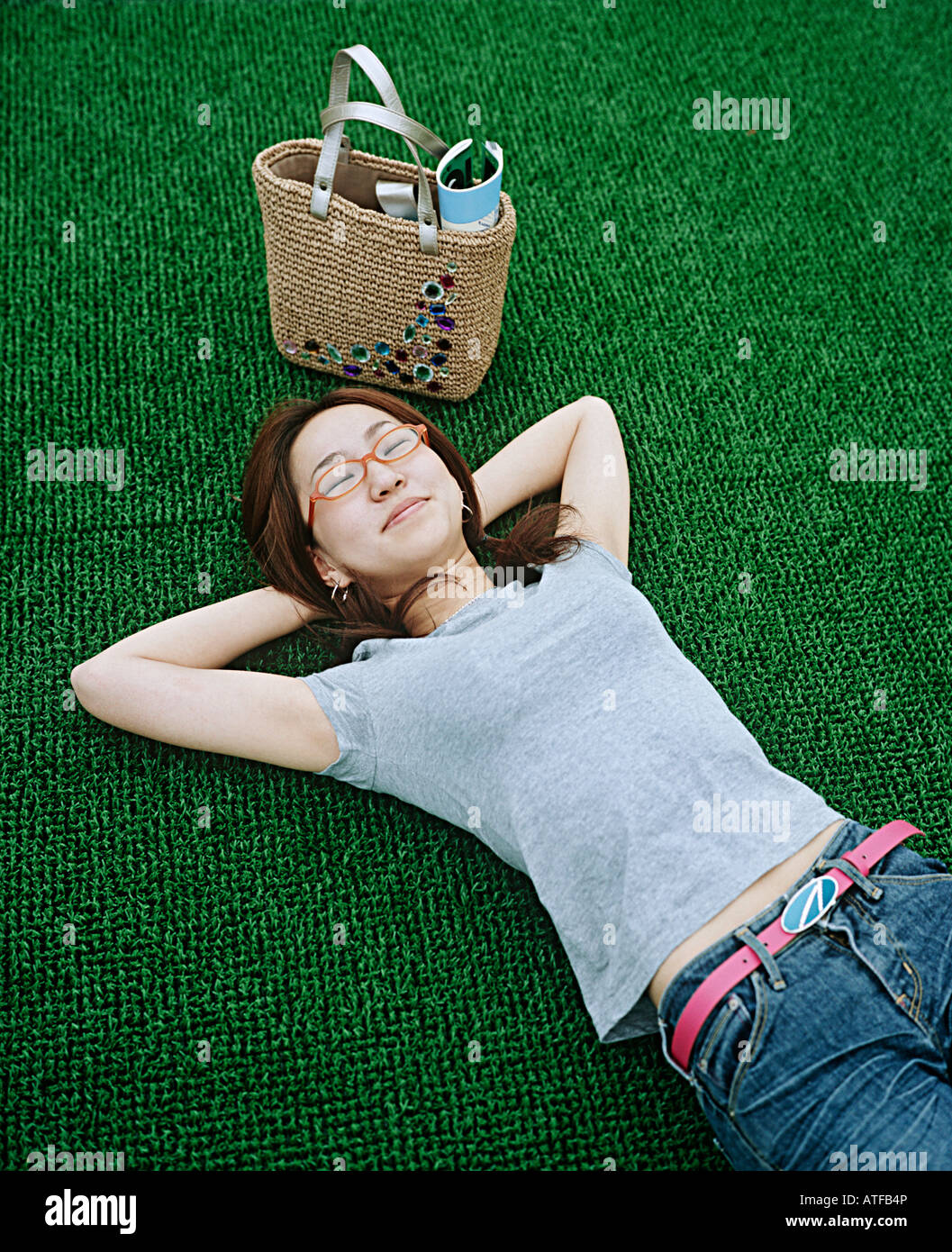 Young woman lying on artificial turf - Stock Image