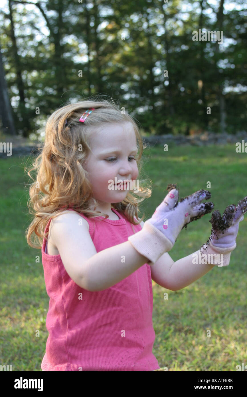 Two year olds enjoy being independent and like messy play in dirt, mud and sand where they learn a lot about shaping - Stock Image