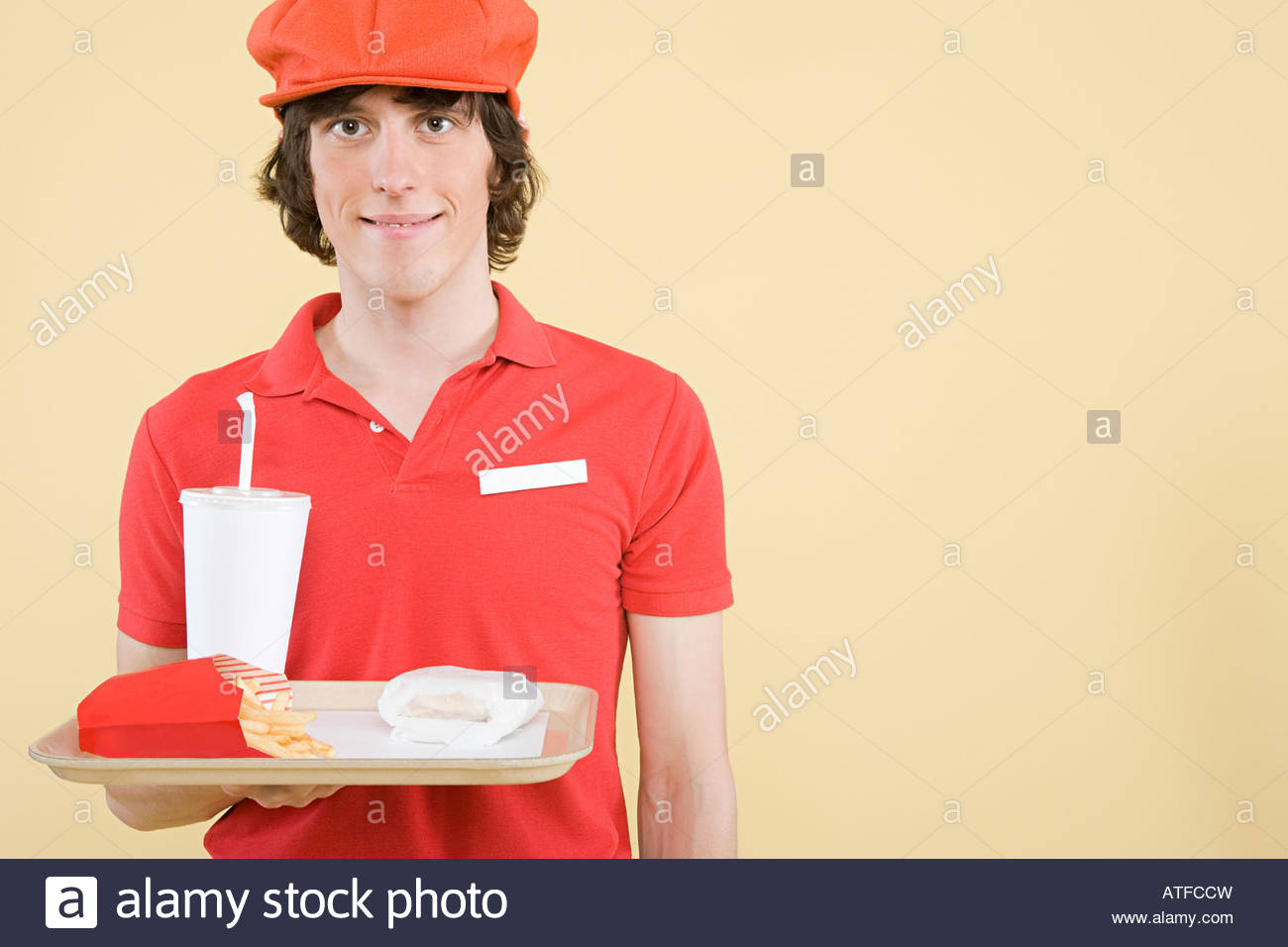 A fast food worker holding a tray of food - Stock Image