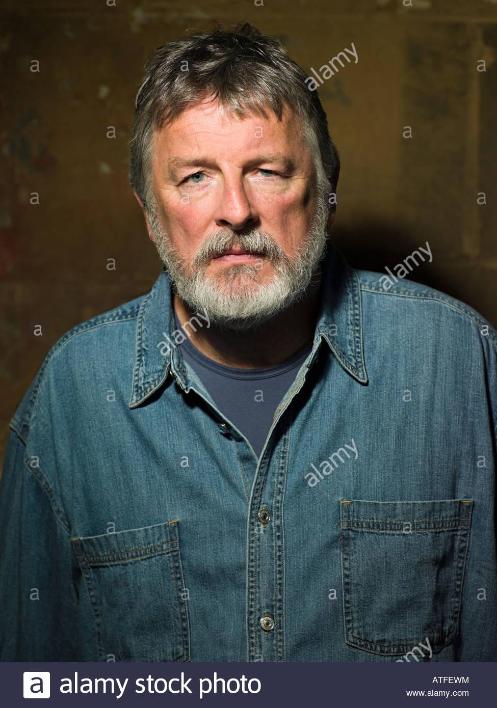 Mature man wearing a denim shirt - Stock Image