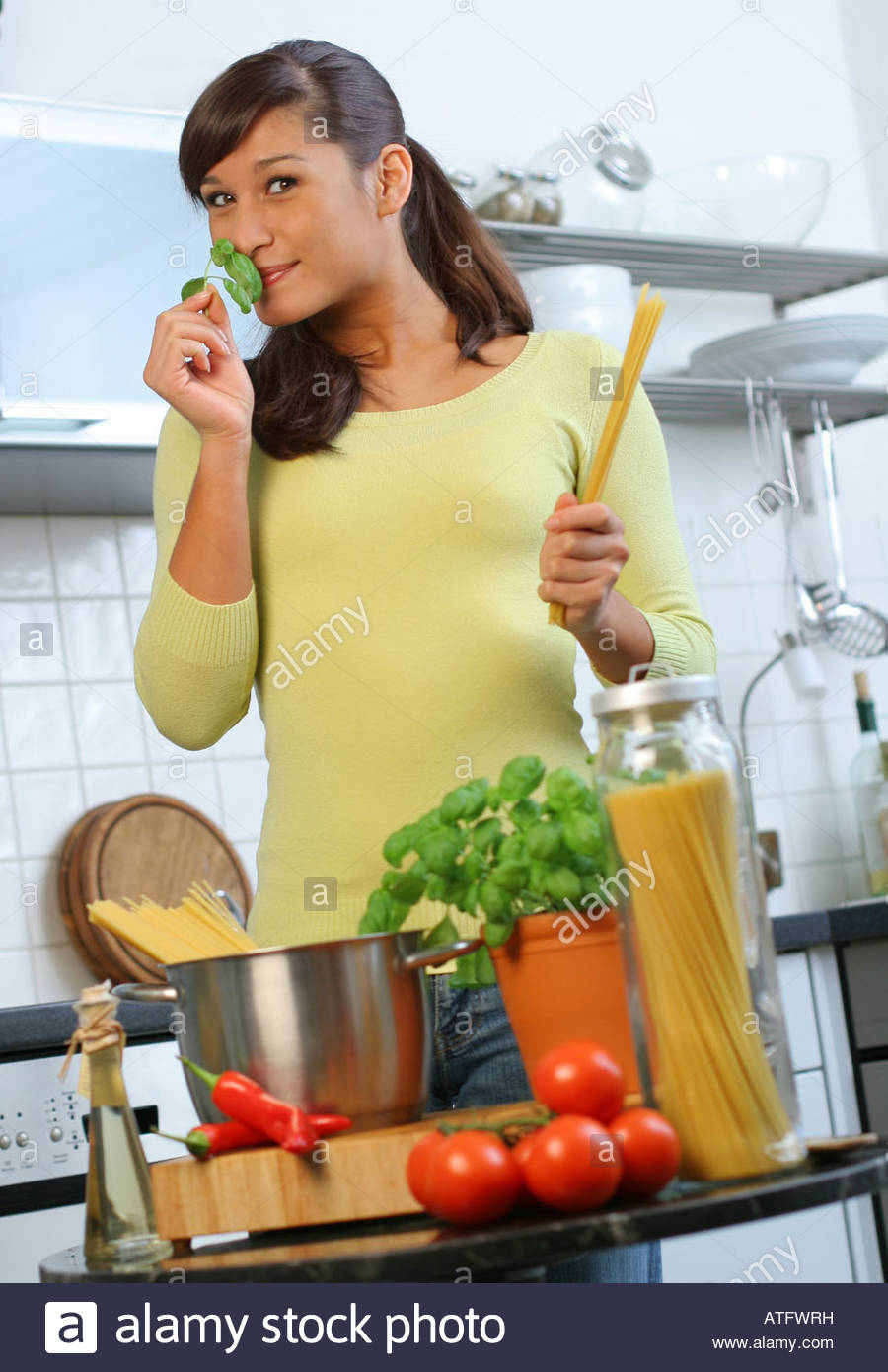 woman cooking with basil Stock Photo