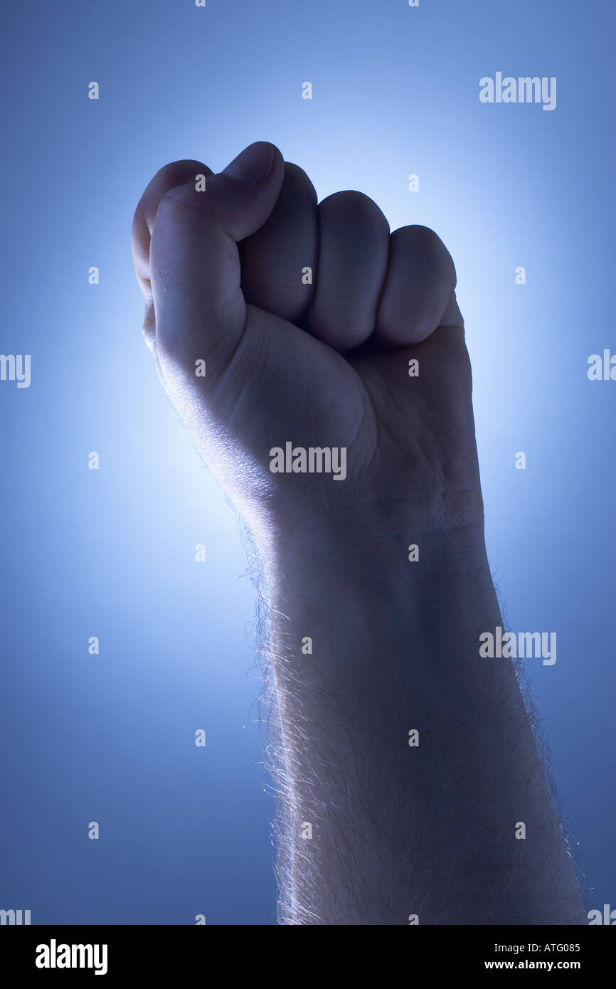 Fist held up in front of spot light - Stock Image