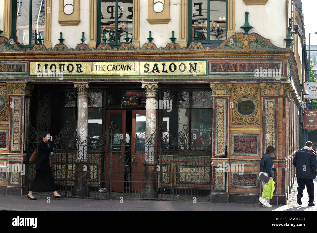 The Crown Saloon. The lower front facade of the famous Belfast landmark of Crown Liquor Saloon Bar Pedestrians walk - Stock Image