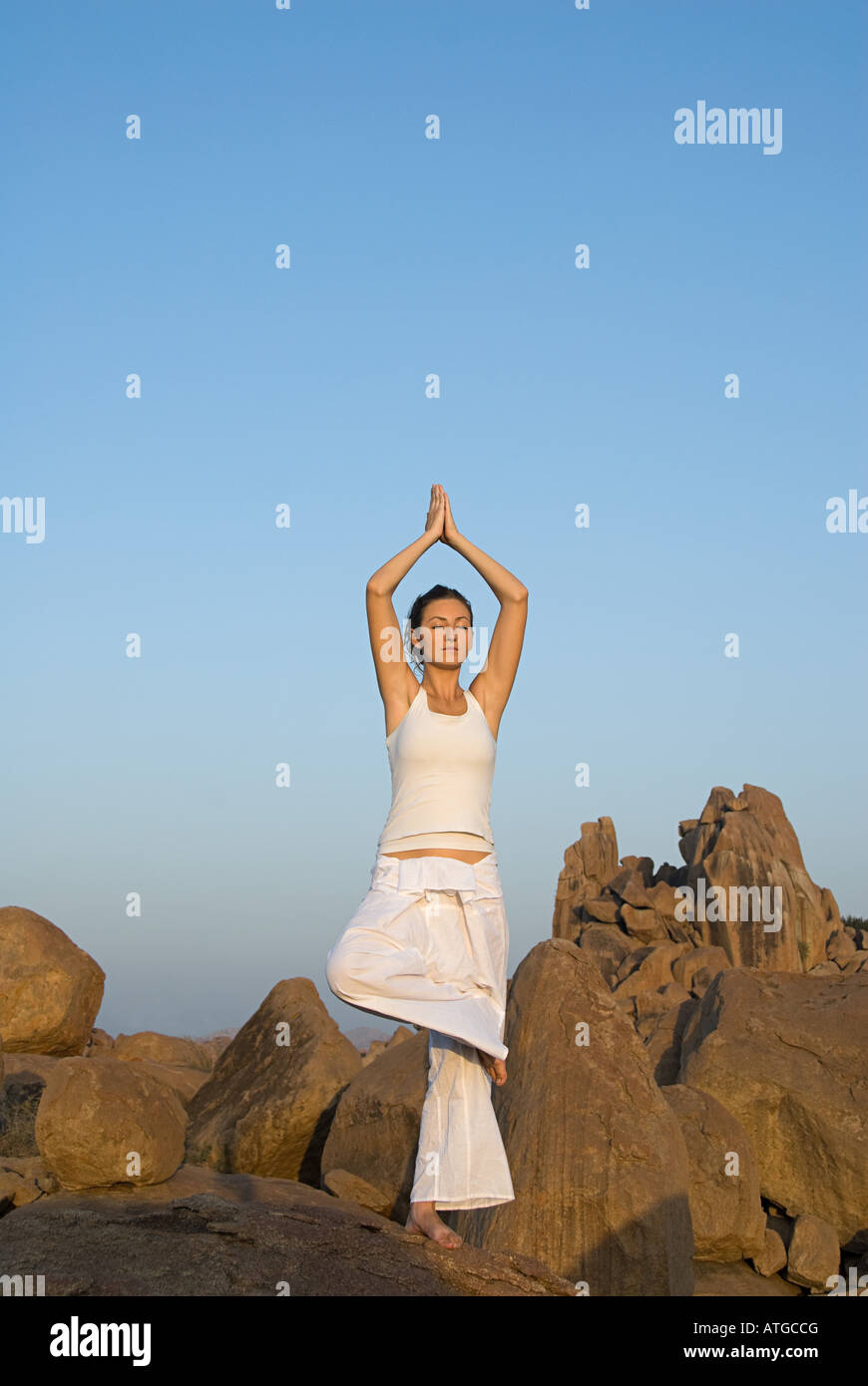 Woman in yoga pose by rocks - Stock Image