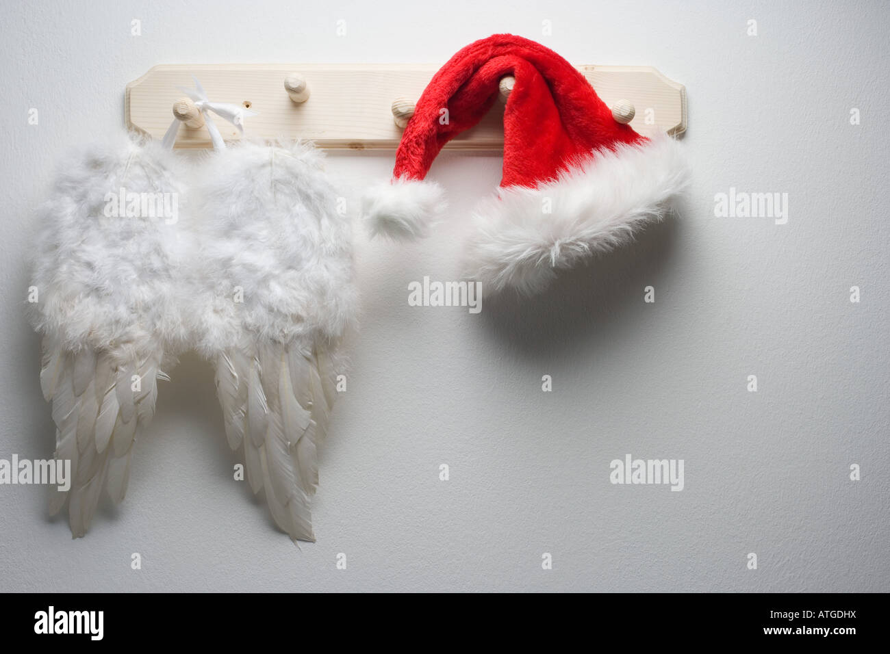 Wings and santas hat hanging on a hook - Stock Image