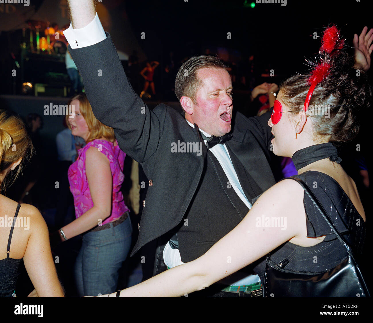 A smartly dressed man in suit and bow tie dances with a woman in a red mask Stock Photo