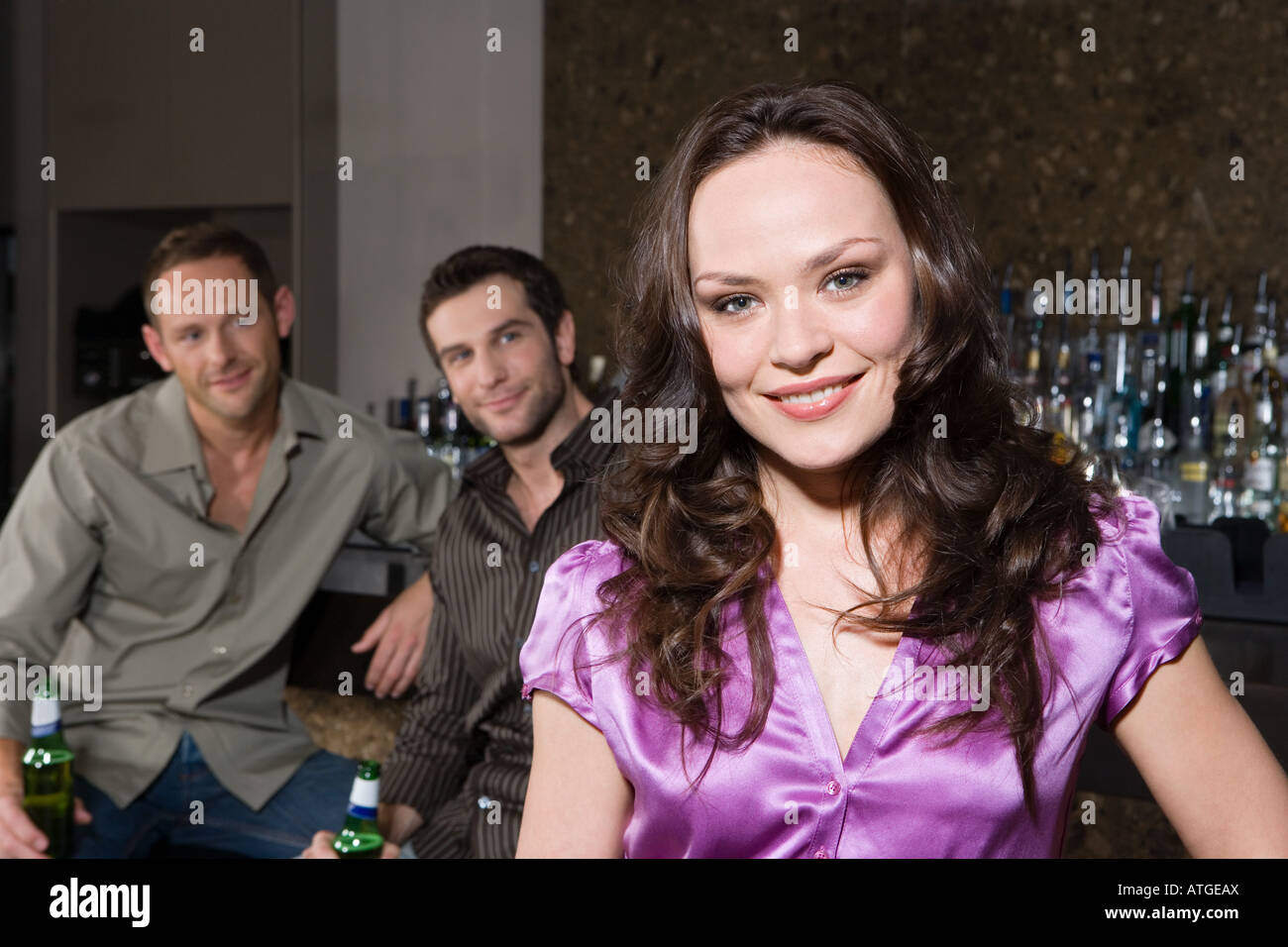 Men looking at a woman in bar Stock Photo