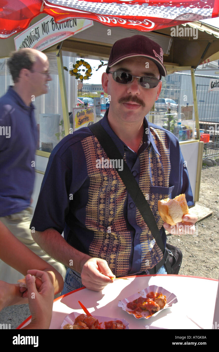 A tourist from New Zealand having a currywurst at a chips stand on Potsdamer Platz. Berlin 2004. Stock Photo