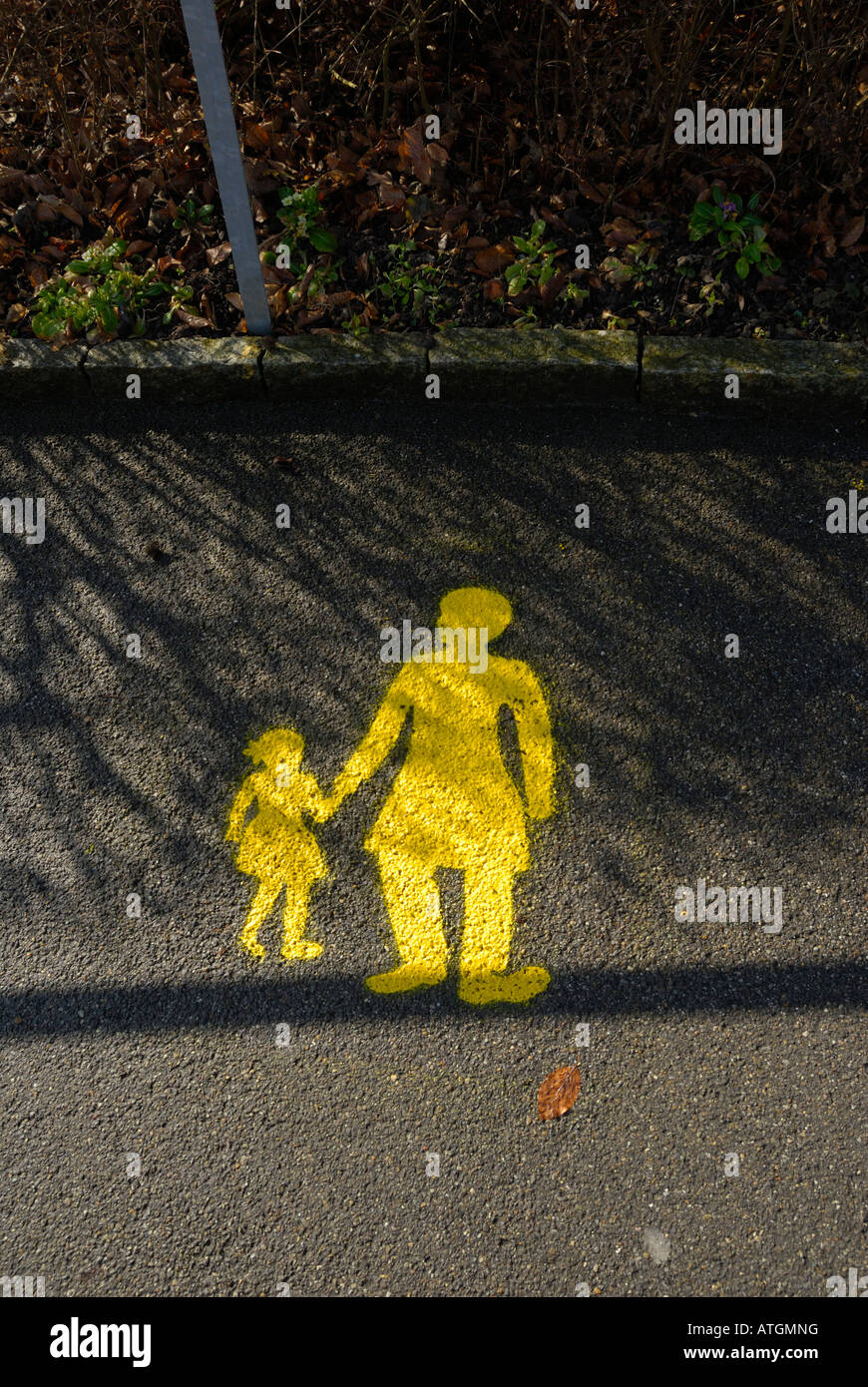 a painted yellow sign on a wet road of a child holding her mothers hand. Stock Photo