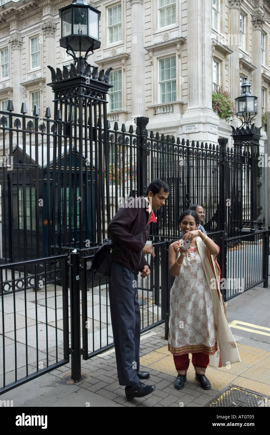 Tourists taking pictures of each other outside the security gates at the entrance to Downing Street London Stock Photo