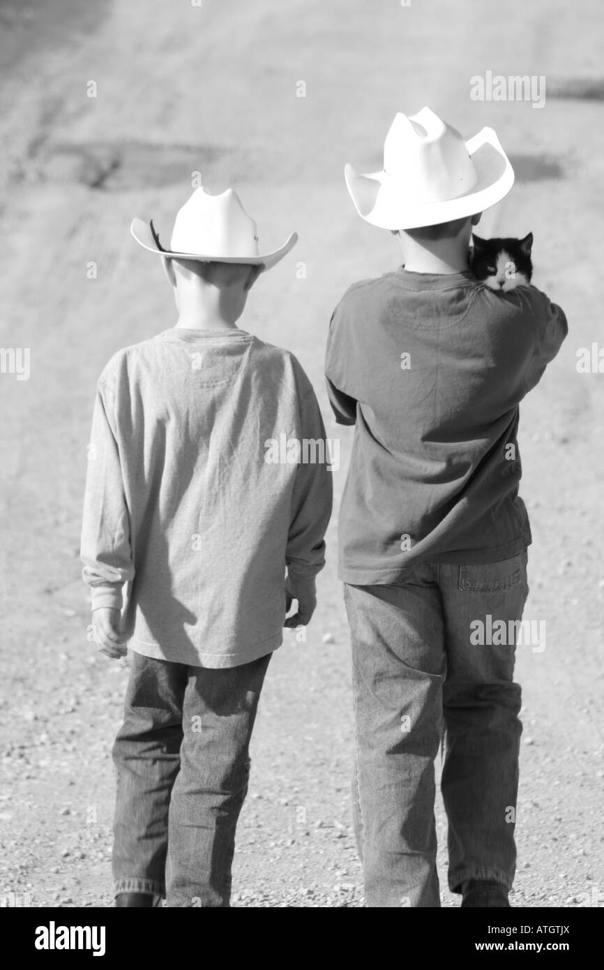 two boys with cowboy hats walking down a farm lane with cat on boys' shoulder - Stock Image
