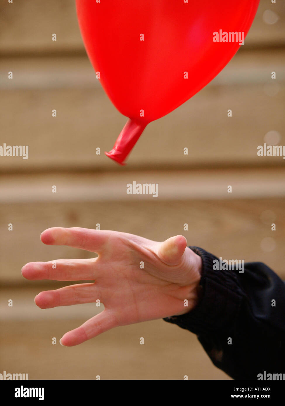 Child s hand letting go of balloon that is flying away because of the air pressure - Stock Image