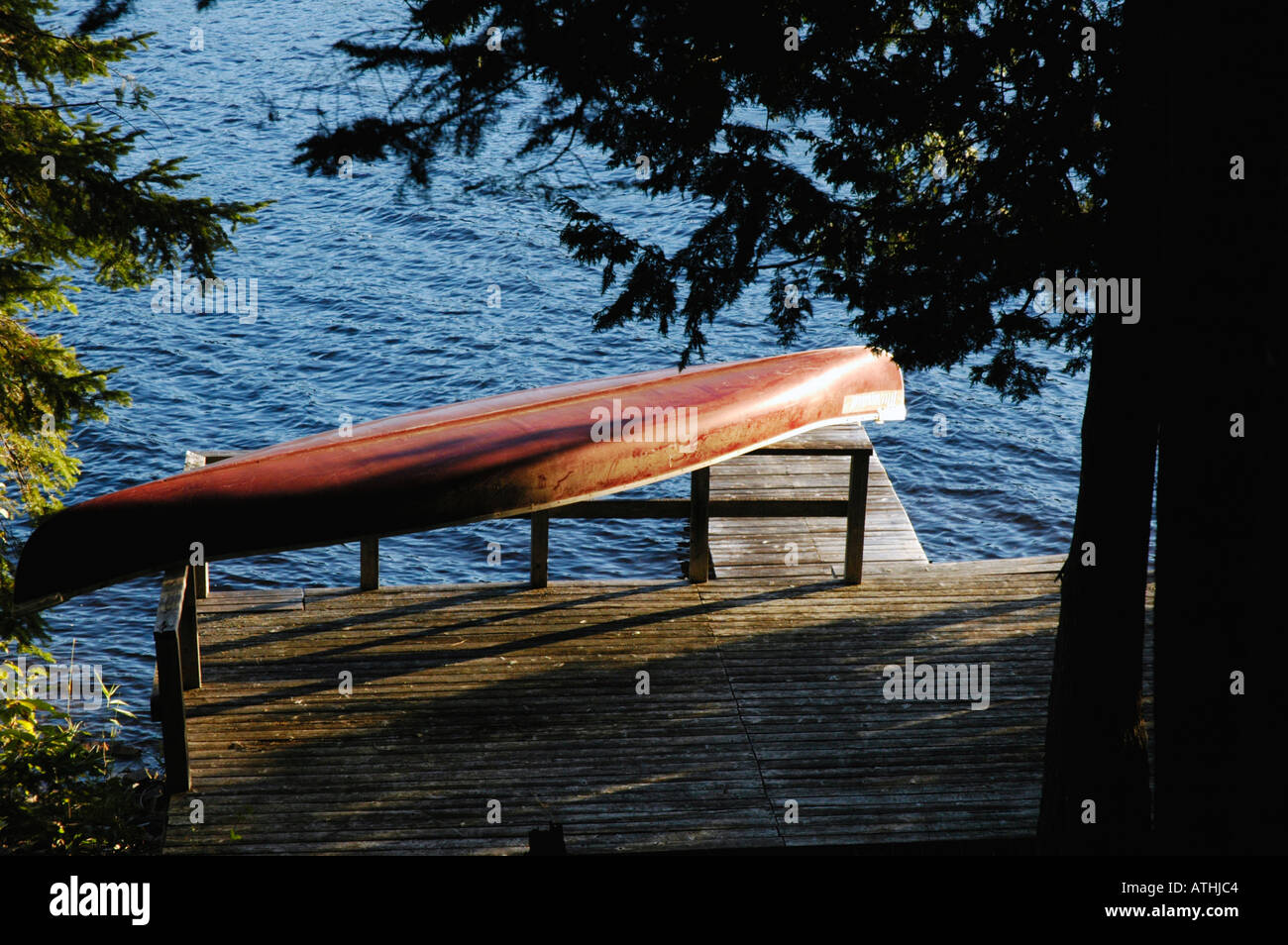 red canoe on dock with slightly windy water and surrounded by forest - Stock Image