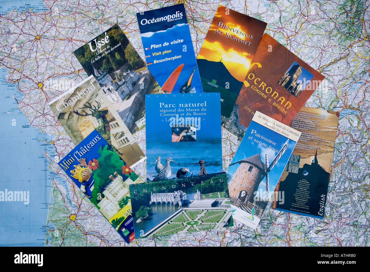 French tourist brochures scattered on map of France - Stock Image