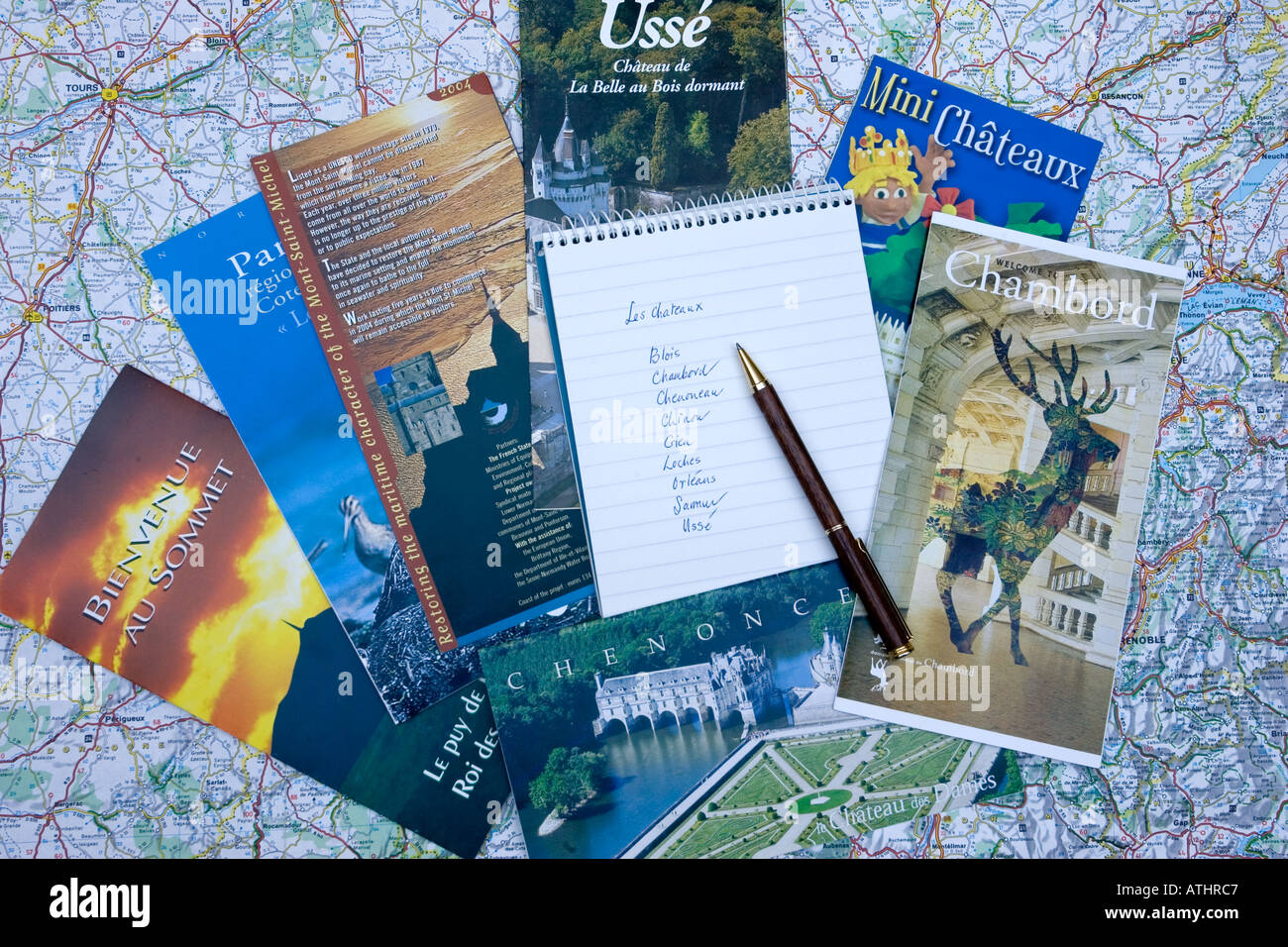 Brochures and notebook spread out on map of France - Stock Image