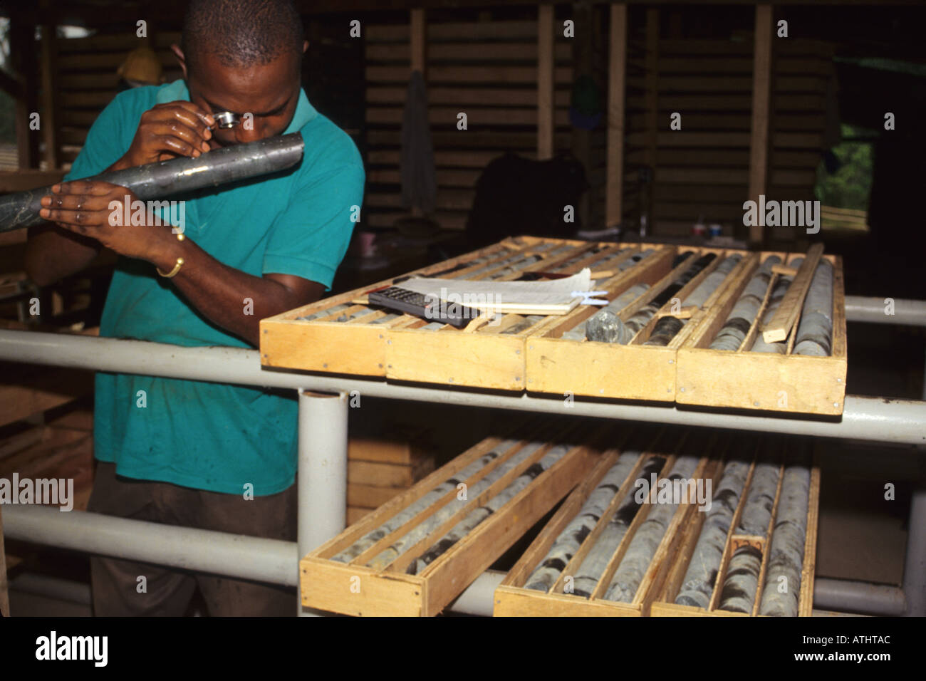Geologist Examining Sample Mineral Core for Gold, SOMIAF Gold Mine, Ivory Coast (Cote d'Ivoire) - Stock Image