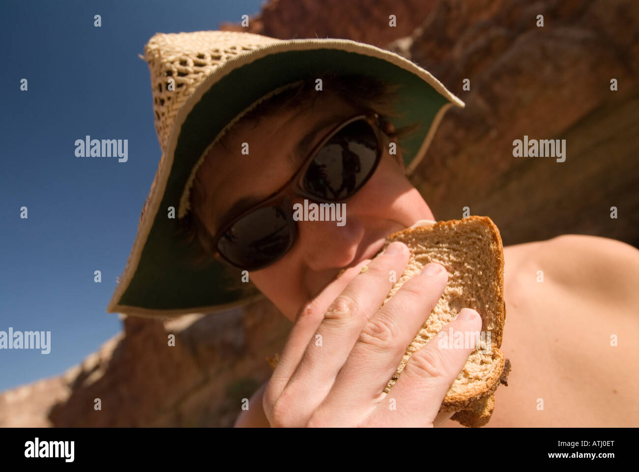 Humerous shot of man taking bite of sandwich during lunch on the Colorado River in the Grand Canyon National Park - Stock Image