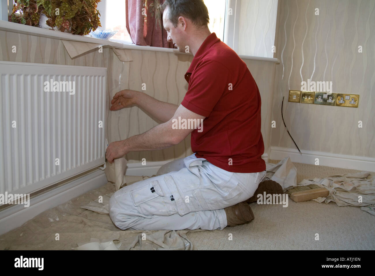 NORTH WALES UK A painter and decorator kneeling down fitting a piece of wallpaper around a radiator - Stock Image
