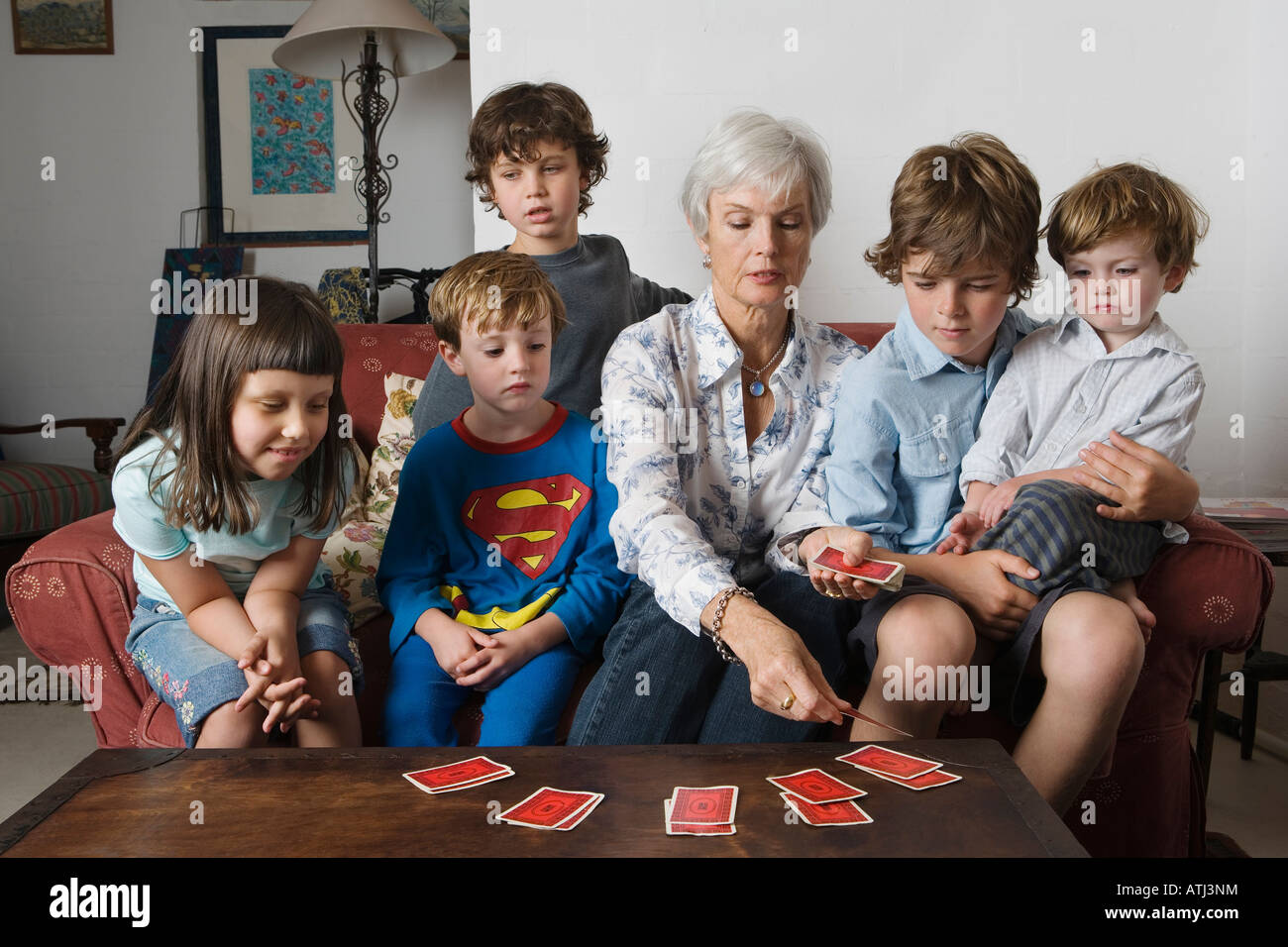 grandmother playing cards with her grandchildren Stock Photo