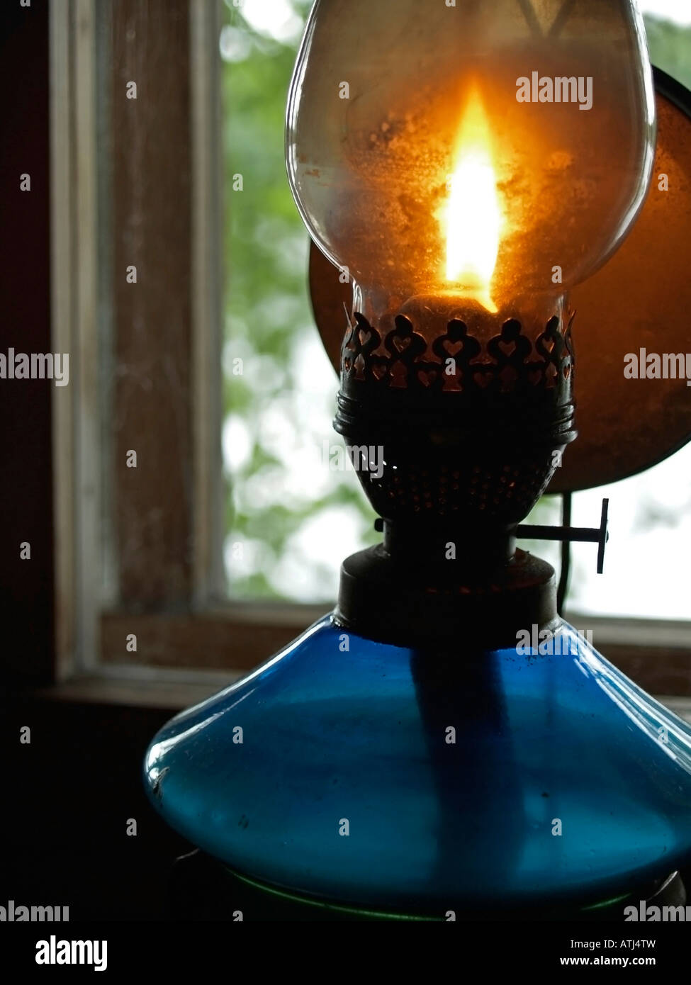 old oil lamp burning with bright flame at window - Stock Image