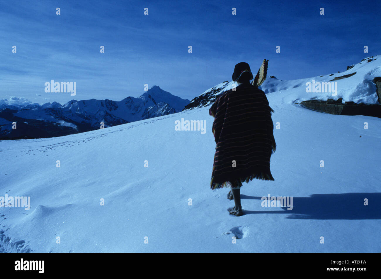 Tarabuco Indian walking on the Chacaltaya peaks of Cordillera Real, south of La Paz, Bolivia. - Stock Image