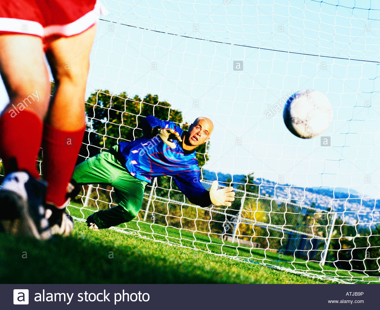 Goalkeeper in front of net diving for a soccer ball in mid air - Stock Image