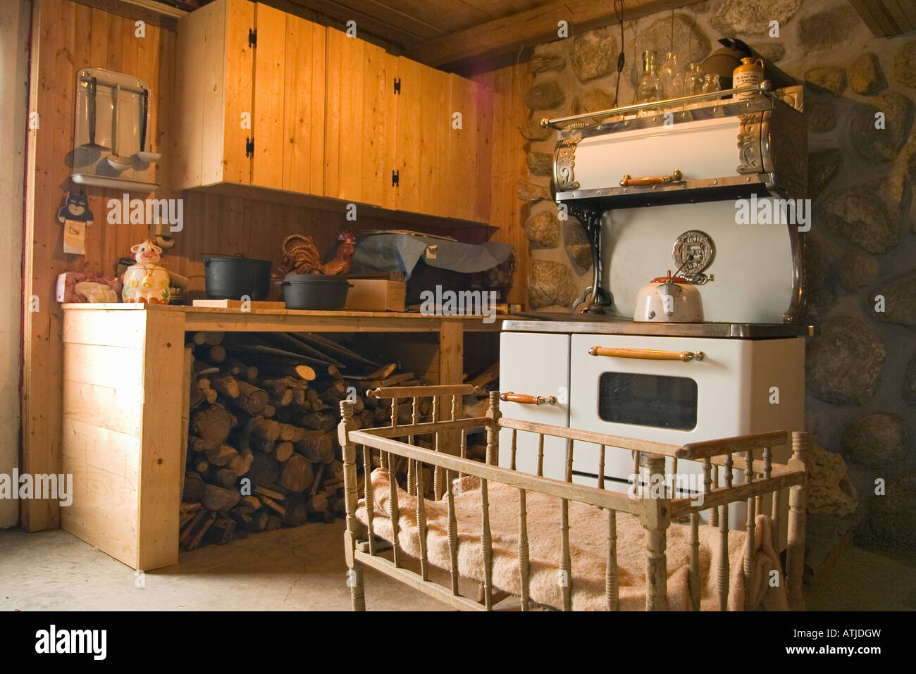 Old baby crib in front of old wood stove in antique kitchen ...