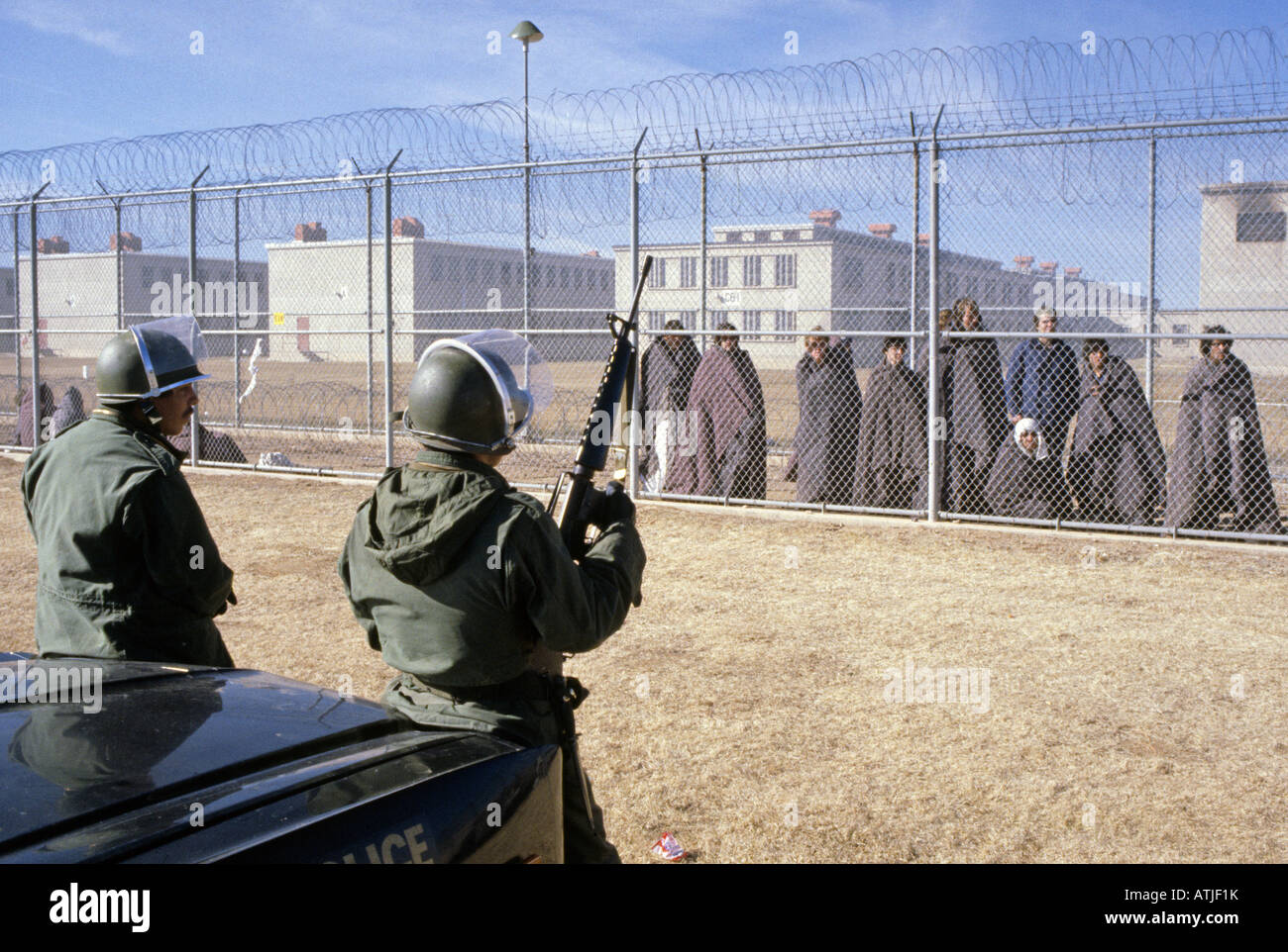 Prisoners who took part in the New Mexico State Penitentiary Riot are guarded by national guard troops - Stock Image