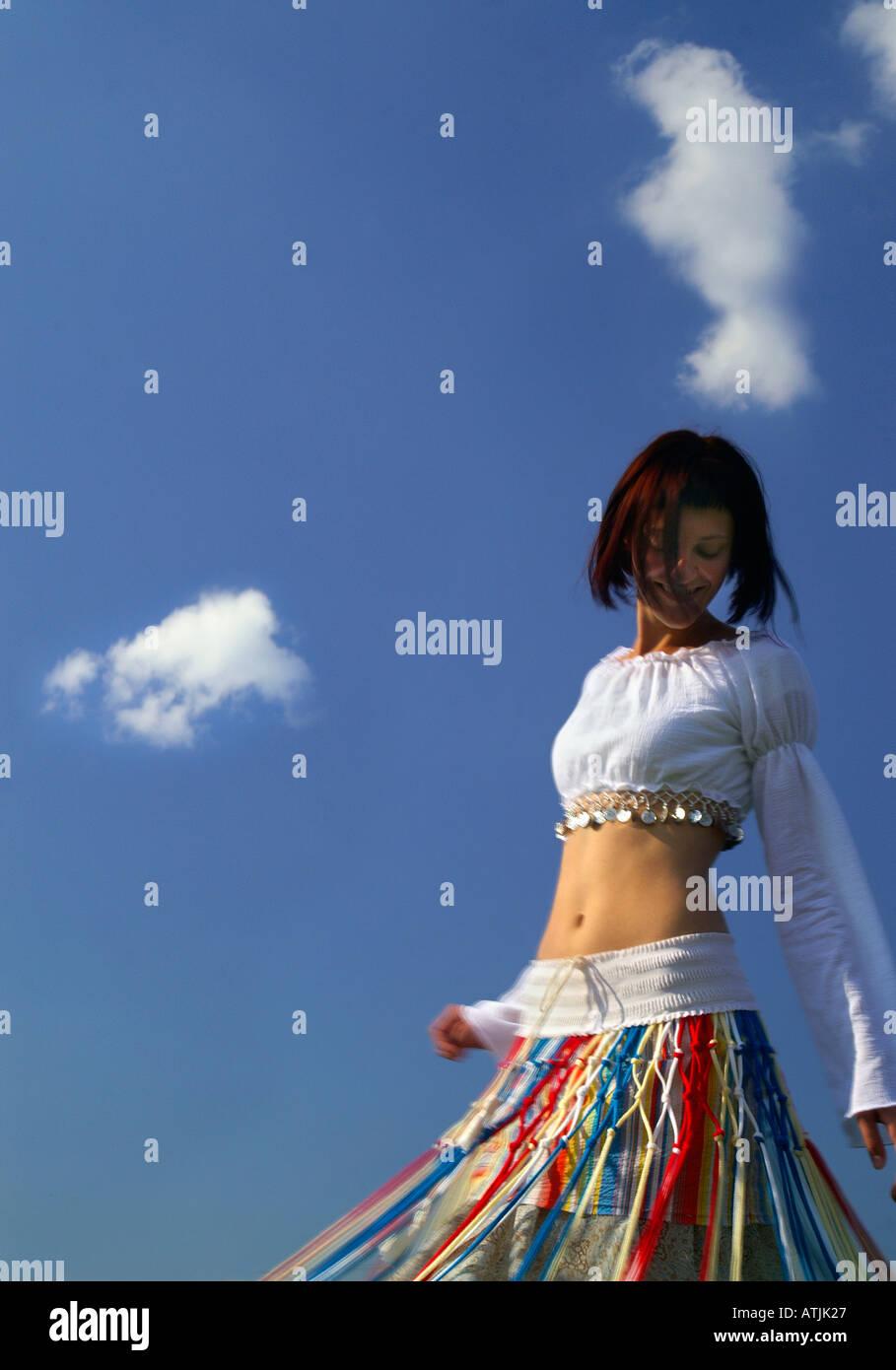 d9db6e1925991 Pretty beautiful slender Girl, Teenage bare Belly Dancer, dancing outdoors  under blue sky