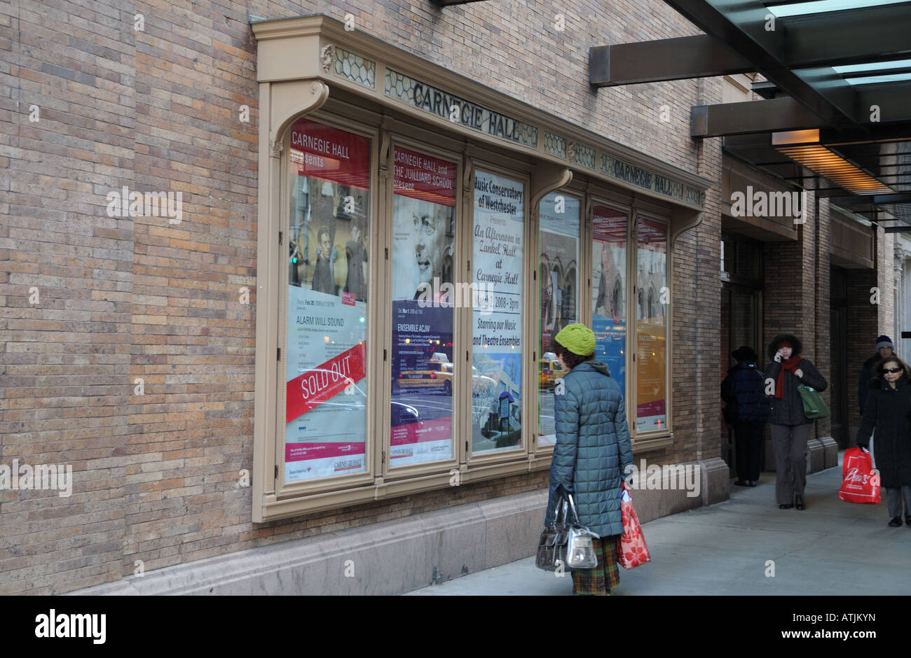 A woman reads ads for upcoming concerts on the outside of New York City's famed Carnegie Hall. - Stock Image