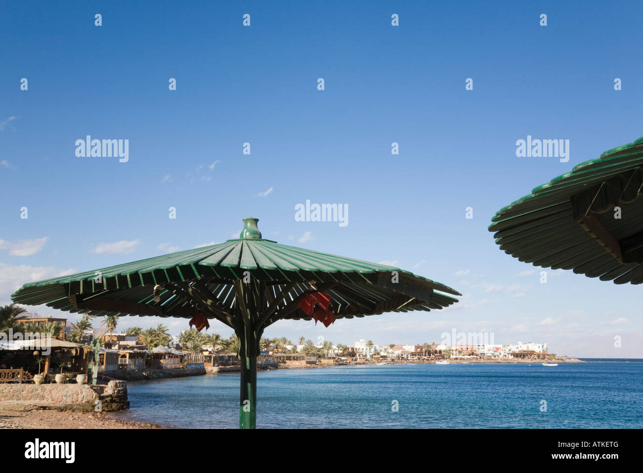 Waterfront beach and bay below sunshades in holiday resort on Red Sea east coast Dahab Sinai Egypt - Stock Image