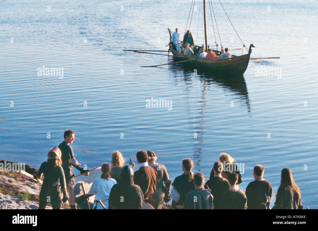Vikings in longship approach shoreline. - Stock Image