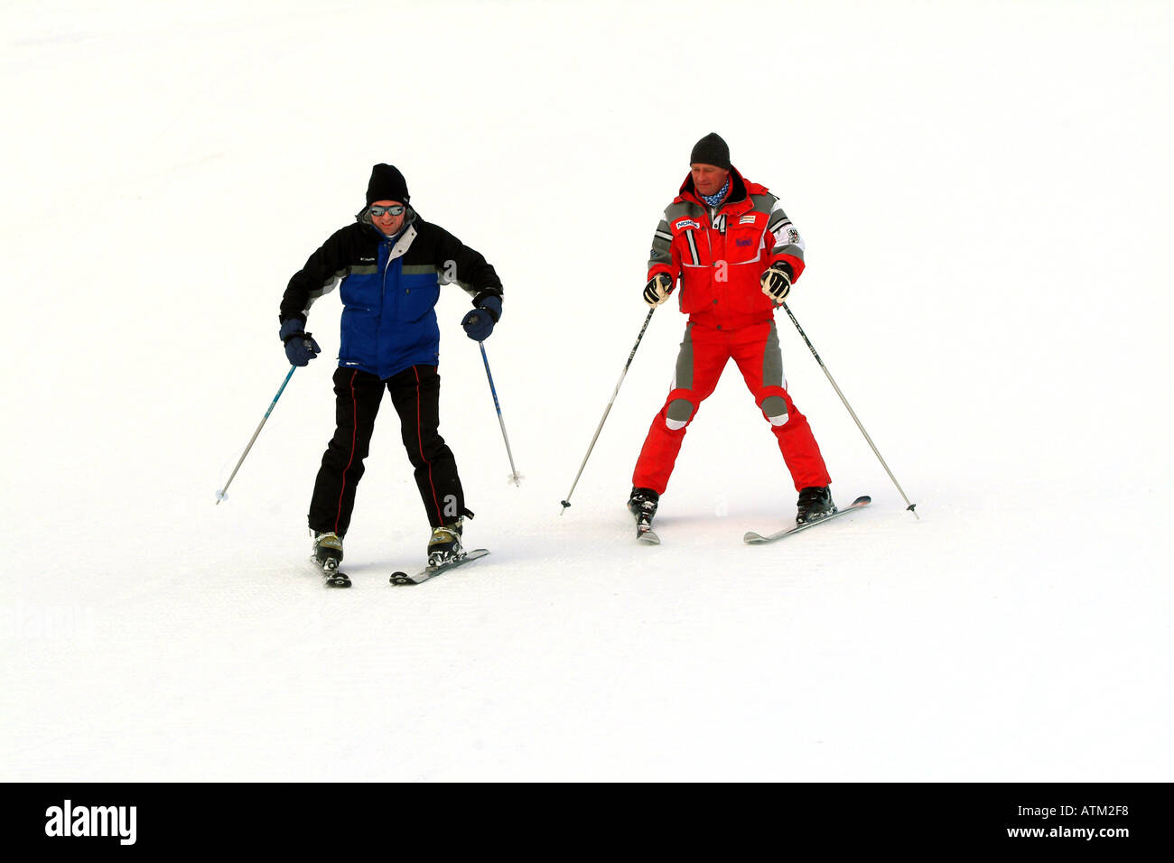 Skier under instruction in the snowplough technique on the pistes of the Schmittenhohe mountain above Zell am See  - Stock Image