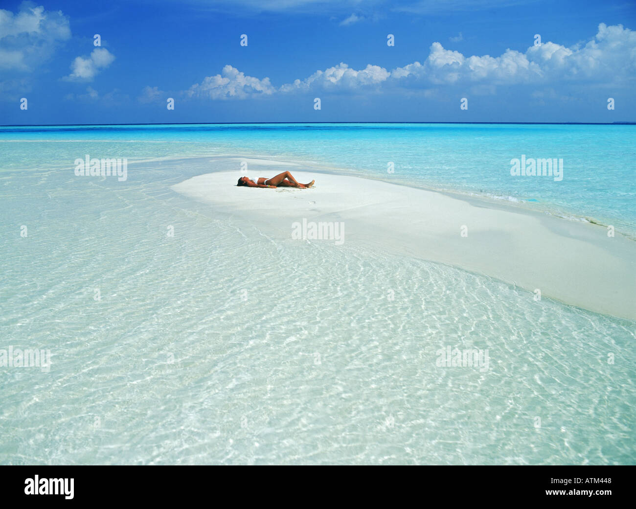 Woman resting on sandbar during holidays to favorite island paradise - Stock Image