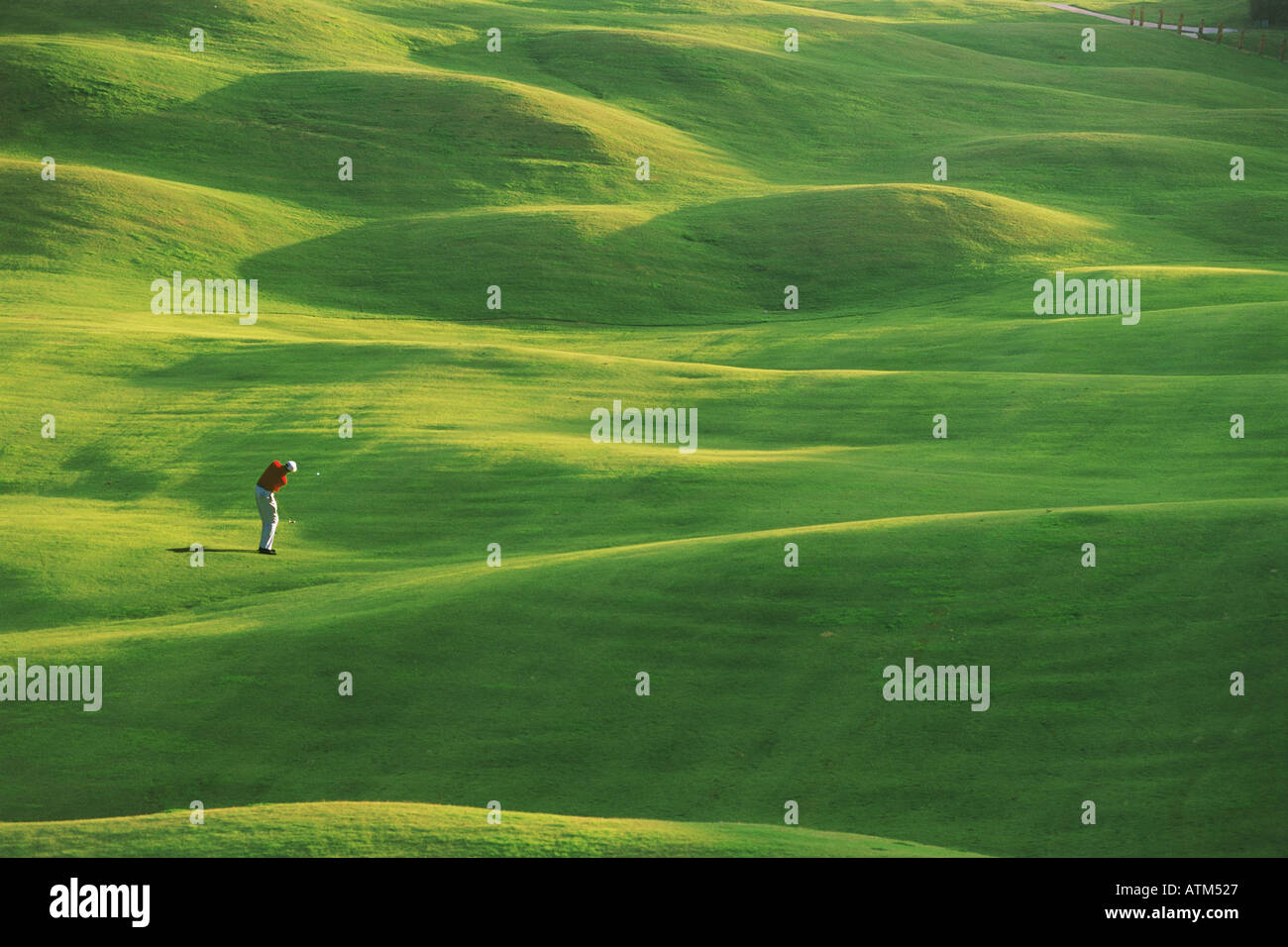 Golfer hitting fairway shot in low light - Stock Image